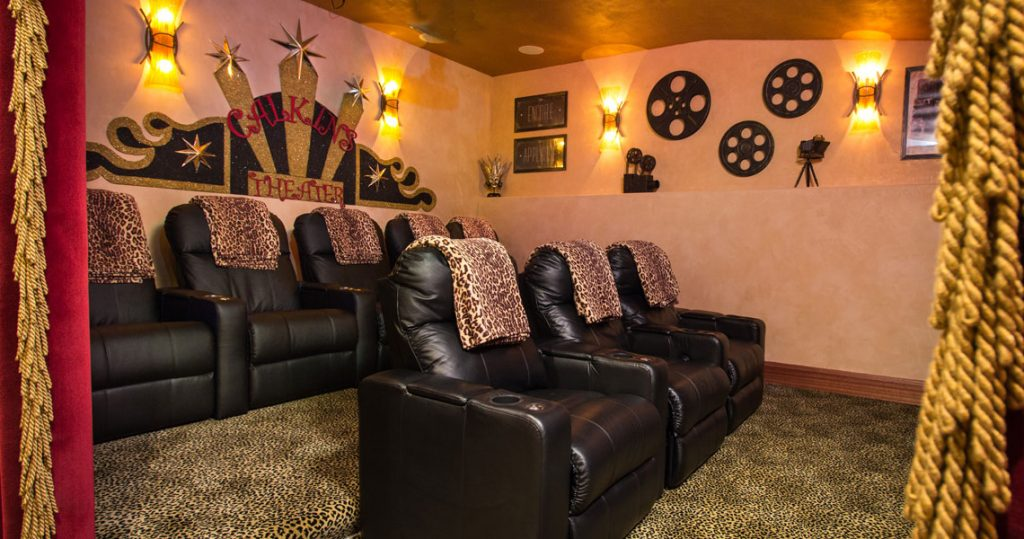 Home theatre with red velvet curtains trimmed with gold bullion fringe