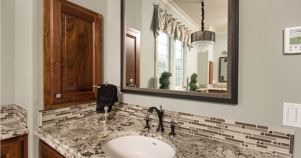 bathroom vanity with glass tile and granite black Brizo faucets