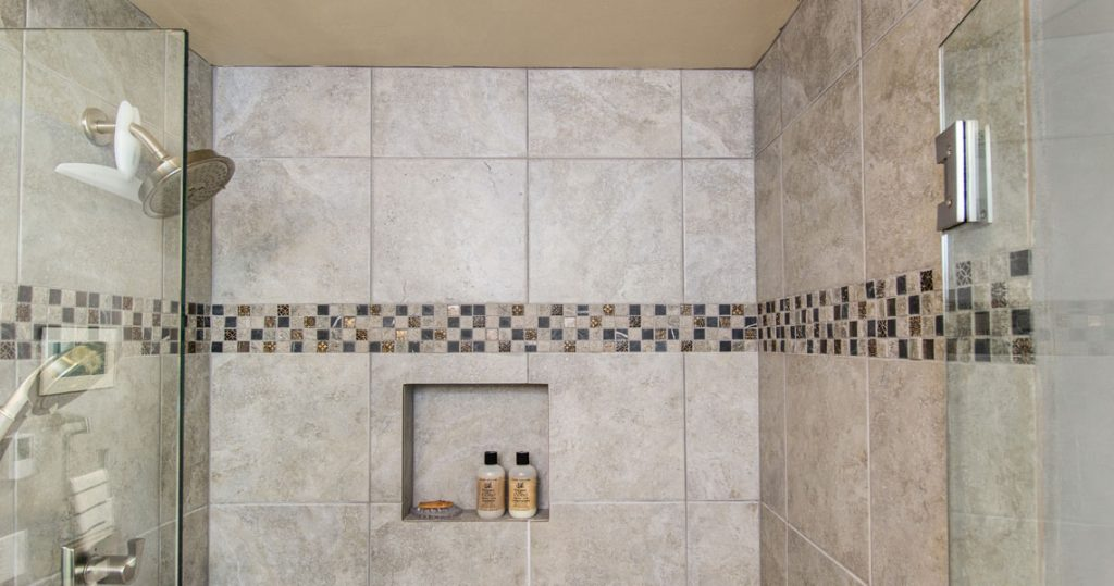 All tiled shower with glass doors in small bathroom remodel