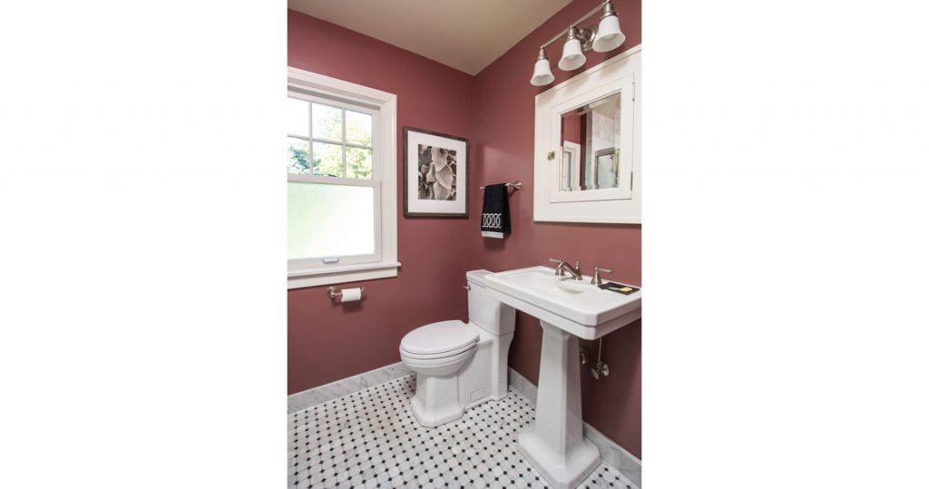 Pedestal sink in small bathroom, mosaic marble floor